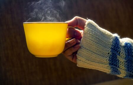 Woman hands holding yellow cup of coffee hot or tea hot, With a winter