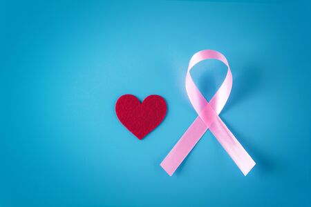 Pink ribbon and red heart on a blue background. Blank copy space.