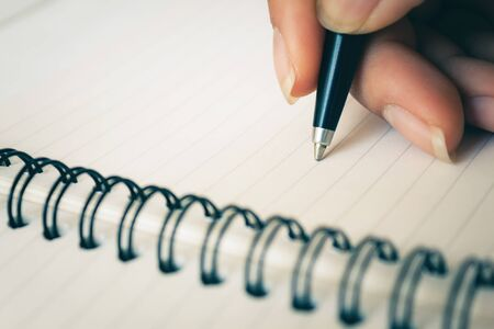 Woman hand with pen writing on white notebook. Focus on the tip of the pen being written. with copy space 免版税图像