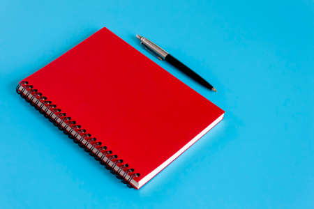 Red notebook and pen on blue background, Concept for Learning and business