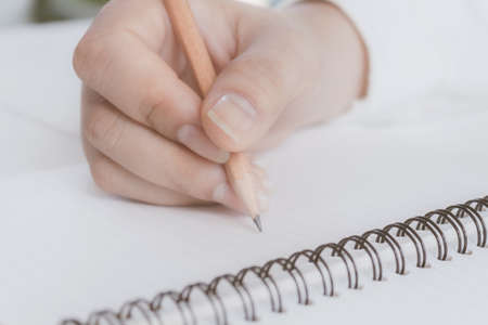 Woman hand with pencil writing on white notebook. with copy space. Standard-Bild