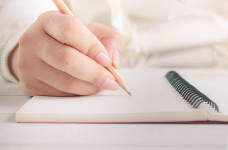 Woman hand with pencil writing on white notebook. with copy space. Concept for education and business
