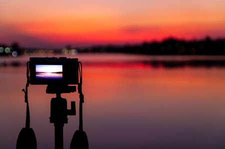 Camera on Tripod is taking photos and time-lapse beautiful sunset. Nature background landscape sunset