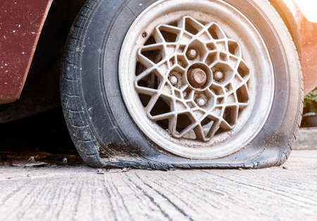 Old tires that are flat, have cracks attached to the wheels of the car. Standard-Bild