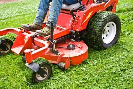 Man op een rij den grasmaaier met gras vast aan de wielen. Lente en de zomer buiten onderhoud.  Stockfoto
