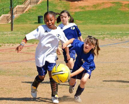 Cumming, Georgia - May 8, 2010 - Young girls chasing the ball during a regular season soccer game between the Fusion Fury and Cheetahs teams. Stock Photo - 7374193