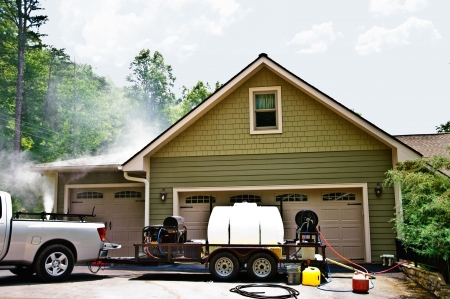 Large pressure washing equipment by a modern house, the spray is showing on the backside.