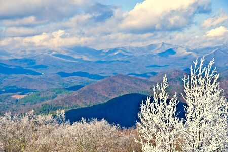 Looking across the mountains on a winter day with snow in the distance and ice on the trees in the foreground. Smoky Mountains. Фото со стока