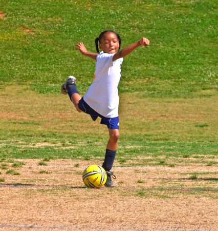 recreation: Forsyth County, Cumming Georgia -  May 8, 2010 - Young girl kicking the ball back inbounds during a soccer game. A regular season game of girls 8 and under. The Fusion Fury vs the Cheetahs.