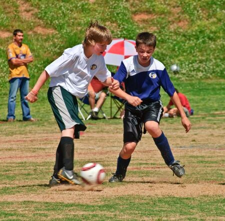 Forsyth County, Cumming, Georgia, USA - May 8, 2010 - Two young boys after the ball during a soccer game. The Fury vs the Tigers, boys under 14, during a regular season game.