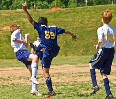 Forsyth County, Cumming, Georgia, USA - May 8, 2010- A group of boys during a soccer game. One has made a kick and the opponent is falling out of the way as others look on. The Fury vs the Tigers, boys under 14, during a regular season game. Stock Photo - 7427878