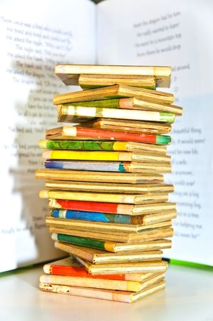 A large stack of childrens books casting a shadow against the background of an open book.
