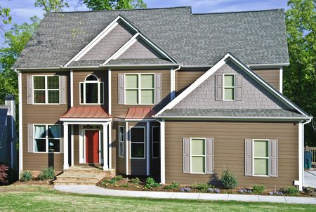 A modern two story house with brown siding and red accents. Grass is just beginning to turn green in the early spring. photo