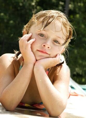 wet suit: A young girl lying beside the pool posing.