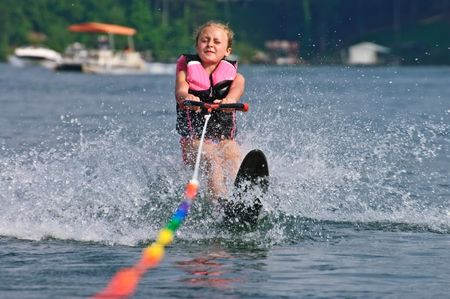 water skiing: A young girl (8 years old) starting her slalom run behind a boat. Stock Photo