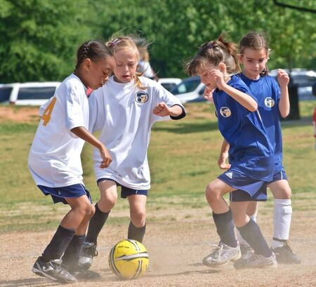 Forsyth County, Cumming Georgia - May 8, 2010 - A group of young girls trying to make a play during a soccer game. A regular season game of girls 8 and under. The Fusion Fury vs the Cheetahs.