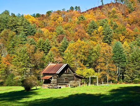 caba�a: Una peque�a caba�a escondida en el valle con todo los colores de oto�o. Las Monta�as Humeantes en Norte GA.