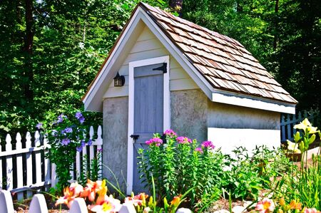 A small garden shed with flowers blooming around it and a white picket fence.