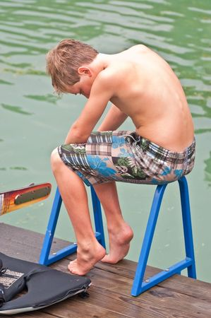 A young boy sitting on a ladder at the water thinking. He has his life jacket and ski beside him. Maybe he's thinking about the end of summer fun. Stock Photo - 7462135
