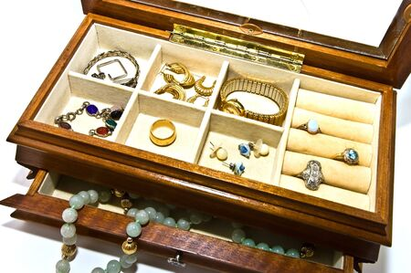 An open jewelry box with bracelets, necklaces, rings, earrings and a watch.