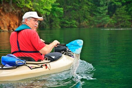 babyboomer: Close up of a man kayaking on a beautiful, quiet lake, hes a babyboomer aged, active person. This was on Lake Jocassee in South Carolina.
