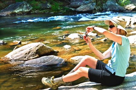 A woman hiker wearing a hat sitting in the sun on a rock by a river taking a photo of the scenery. This is on Raven Rock Trail in Rabun County, Georgia, Tallulah Falls Area on the Chattooga River. photo