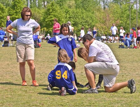 Forsyth County, Cumming Ga. -  April 17, 2010 - Man and woman coaching young girls soccer team giving some instructions during a game between the Fusion Fury and the GA Express.