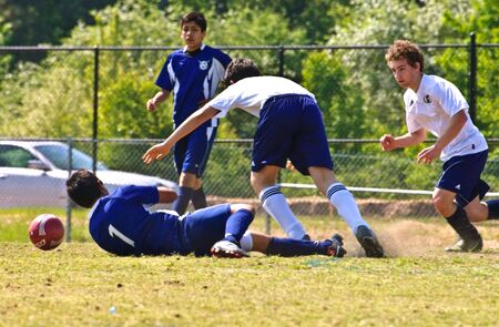 Forsyth County, Cumming Ga. - April 17, 2010- Boys falling while trying to make a play for the ball during a regular season soccer game. The Fusion Storm vs The Dahlonega Dusa at a regular season game.