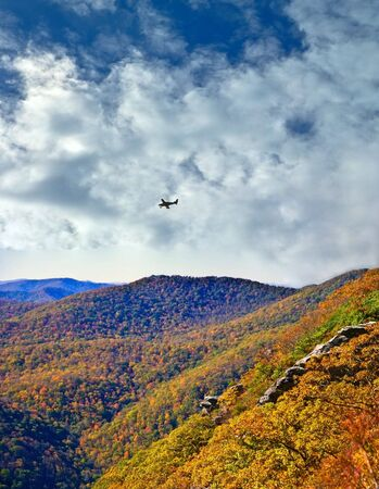 This is an area in North Carolina called Pickens Nose, looking south toward Georgia.  There are rock formations for viewing and climbing. An autumn scene with sky and an airplane in the Smoky Mountains. photo
