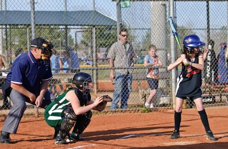 Forsyth County, Cumming GA - March  31, 2010 - Action at home plate during a game, batter, catcher, and umpire. 9 and 10 year old girls ASA softball team, the Coal Mountain Lady Bulldogs vs the Central Green Vipers.