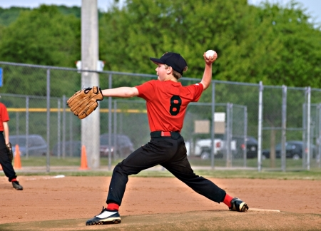 baseball caps: A young pitcher ready to throw to the batter.