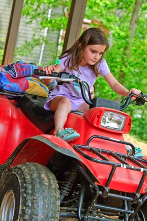 quad: Young girl sitting on an ATV ready to learn how to drive it. She has a sucker in one hand.
