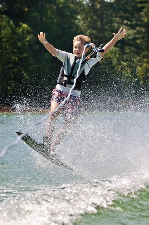 A young boy losing control of his ski and releasing the rope. photo