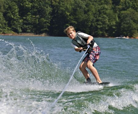 A young boy doing a side slide on his trick ski.