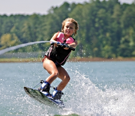 A young girl jumping waves on her wakeboard. Standard-Bild