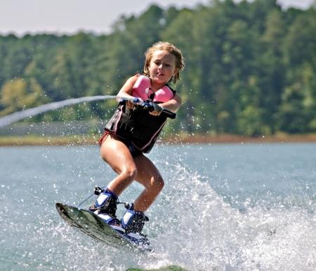 despertarse: Una ni�a saltando las olas sobre su wakeboard.  Foto de archivo