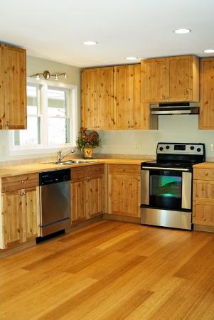 대나무 바닥과 소나무 캐비닛이있는 작고 새로운 부엌.