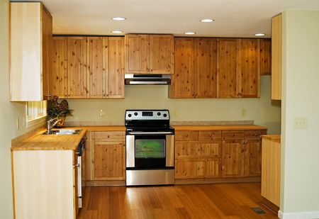 appliances: The interior of a new, small, kitchen with bamboo flooring and pine cabinetry.
