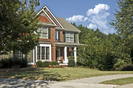 suburban neighborhood: The front of a new, modern, home showing the yard, driveway and sidewalk.