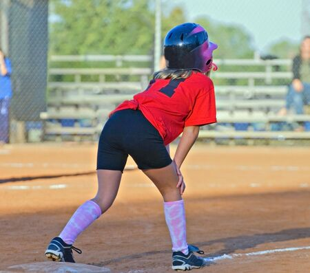 A young girl softball player on third base ready to run into home. Stock Photo