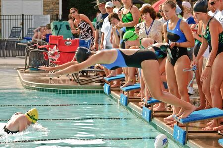 long lake: Cumming, Georgia, USA - June 18, 2010 - Teenage girls during a swim meet relay competition in Forsyth County, Cumming GA, June 18, 2010. The Lake Forest Lightening vs the Long Lake Marlins. Team members ready to dive in for their lap. Editorial