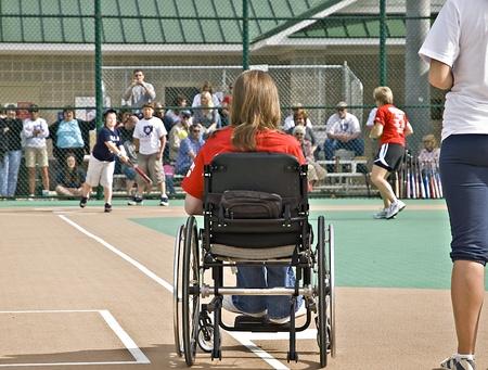 enfants handicap�s: Cumming, GA, USA - 18 avril 2009 : Un gar�on de besoins sp�ciaux faisant un hit, tandis que le joueur de premier but en fauteuil roulant montres. Comt� de Forsyth, Cumming, GA, 18 avril 2009, le Reds vs le Blues.