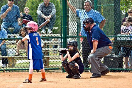 an umpire: Cumming, GA, USA - April 18, 2009 : A young girl  at bat during a softball game. Forsyth County, Cumming, GA, April 18, 2009. A regular season game of the Lady Gators vs the Bennet Park Blues.
