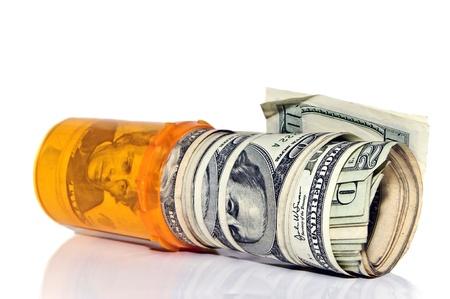 recetas medicas: Una botella de p�ldora de prescripci�n con rollos de dinero en efectivo en el mismo.  Concepto o met�fora de costo de los medicamentos.