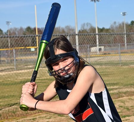 equipment: A young softball palyer with safety equipment on ready to hit the ball. Stock Photo