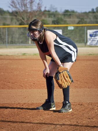 A preteen girl playing her position during a softball game with her safety eauipment on. photo