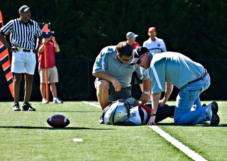 Forsyth 카운티, Cumming, 조지아 - 2010 년 10 월 2 일 - 해적판과 독수리 사이 정규 리그 경기 도중 코치에 의해 검사를 받고 필드에 부상 된 선수. 에디토리얼