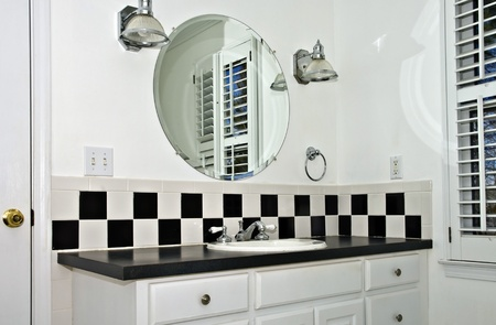 The sink area of a small bathroom with black and white tile.