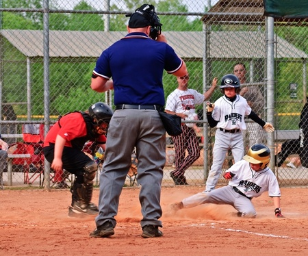 Cumming, GA, USA - April 19, 2010 - A little league baseball catcher tagging the runner out on homeplate at a game in Forsyth County, Cumming GA, 4-10-2010.  A regular season game between the Bulldogs and the Raiders. Editorial