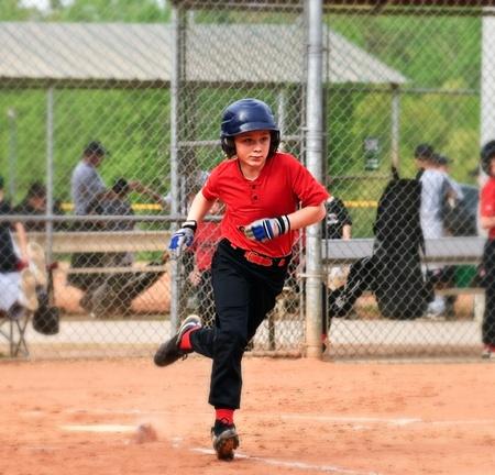 Después de hacer un éxito de una pelota de béisbol joven jugador corre a primera base.  Para el efecto de desenfoque gaussiano.